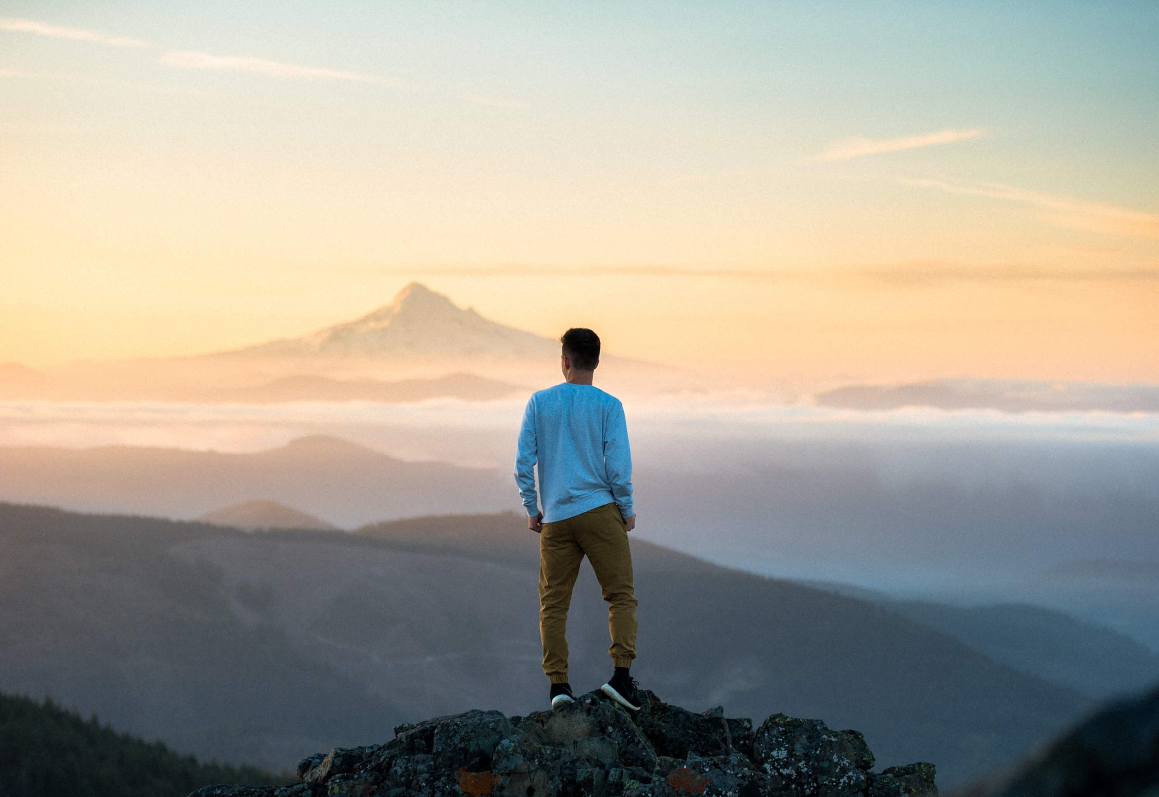 Man stood on top of mountain
